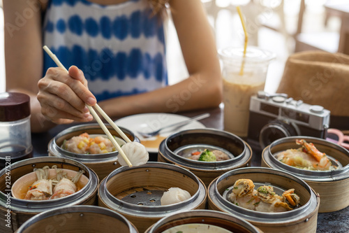 Young woman traveler eating local food(dim sum) at phuket, Thailand