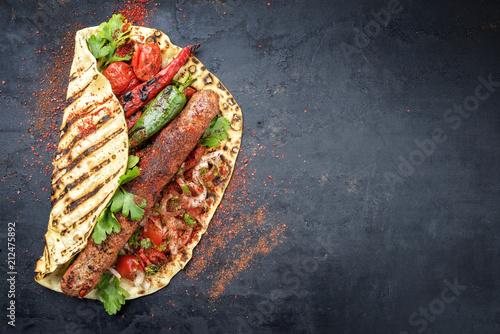 Traditionelles Adana Kebap mit Tomaten und Salat auf Fladenbrot  auf einem Board mit Textfreiraum rechts