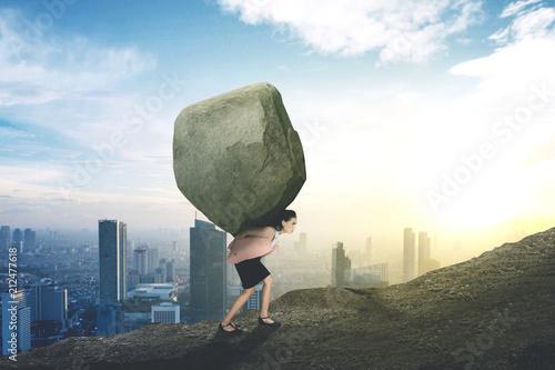 Fototapeta Caucasian businesswoman lifting stone on the hill
