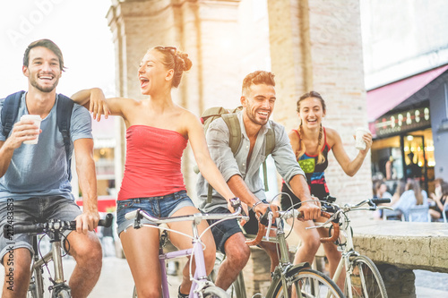 canvas print motiv - DisobeyArt : Happy friends riding bicycles in city center and drinking coffee