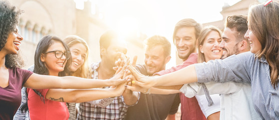 Young millennials friends stacking hands together