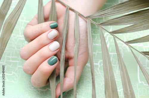 Female hands with green nail design Fotobehang