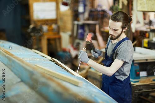 Obraz na plátně Young shipbuilding master hammering chisel into wooden board on vessel construct