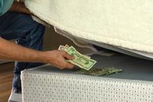 Man Stashing Putting Money Und...