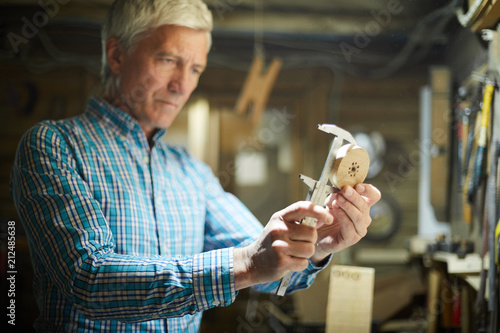 Fotografía Professional engineer measuring diameter of round wooden workpiece in his workro