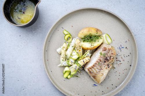 Modern gebratenes Kabeljau Filet mit weißen Spargel Spitzen und Bratkartoffel  als Draufsicht auf einem Teller