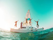Leinwanddruck Bild Happy crazy friends diving from sailing boat into the sea