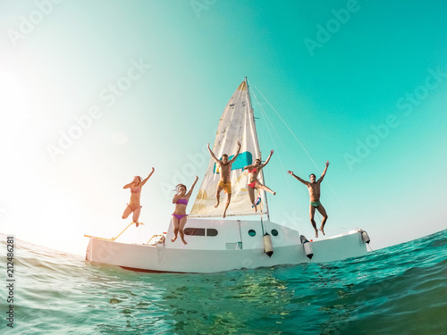 Foto Happy crazy friends diving from sailing boat into the sea