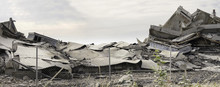 Industrial Concrete Building Destructed By Strike. Disaster Scene Full Of Debris, Dust And Crashed Buildings
