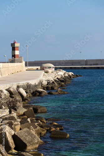 Deurstickers Poort Lighthouse in Monopoli port in front of Castle of Carlo V, Adriatic Sea, Apulia, Bari province, Italy