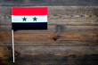 Syrian flag concept. small flag on dark wooden background top view copy space