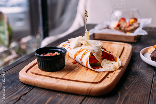 Meat kebab with chips topping with sauce and served with tomato salad on wooden plate.