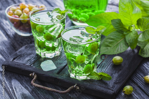 Foto op Plexiglas Cocktail green gooseberry cocktail with ice and fresh mint on a black wooden table