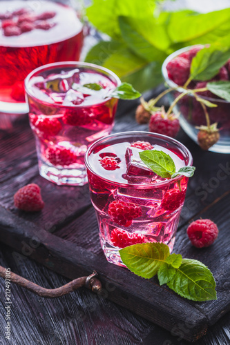 Foto op Plexiglas Cocktail Red raspberries cocktail with ice and fresh mint on a old wooden table