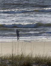 Man On A Beach Fly Fishes In T...