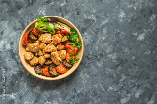 Pieces of baked meat with grilled vegetables on a plate.