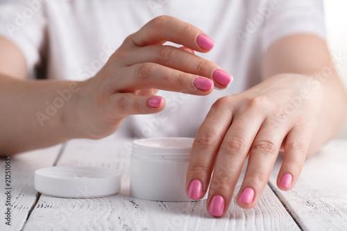 Láminas  Closeup shot of hands applying moisturizer