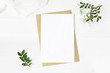 canvas print picture - Feminine wedding stationery, desktop mock-up scene. Blank greeting card, craft envelope, baby's breath flowers, silk ribbon and lentisk branches. Old white wooden table background. Flat lay, top view.