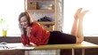 Attractive woman lays on office desk while talking on phone. Playful and flirty female office worker laying on top of office table swinging her legs back and forth and having phone conversation.