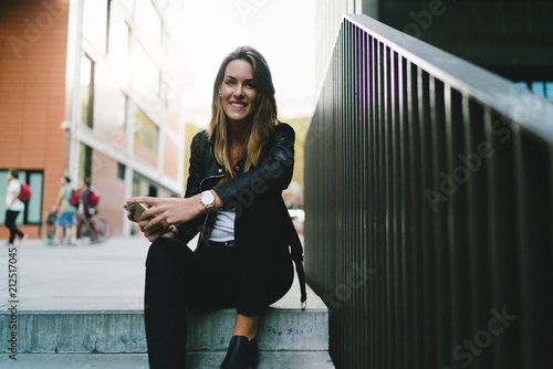 Charming smiling tourist girl with long blonde hair wearing stylish clothes relaxing on a steps of street staircase and typing messages on mobile phone to her friends about her vacation.