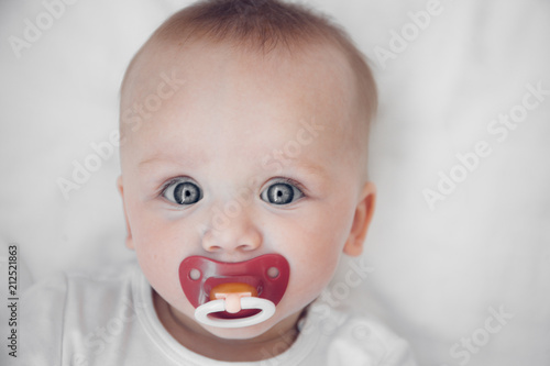 portrait of a cute baby with soother lies on his back on a white sheet Tablou Canvas