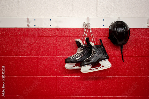 Photo  Hockey skates and helmet hanging in locker room with red background and copy