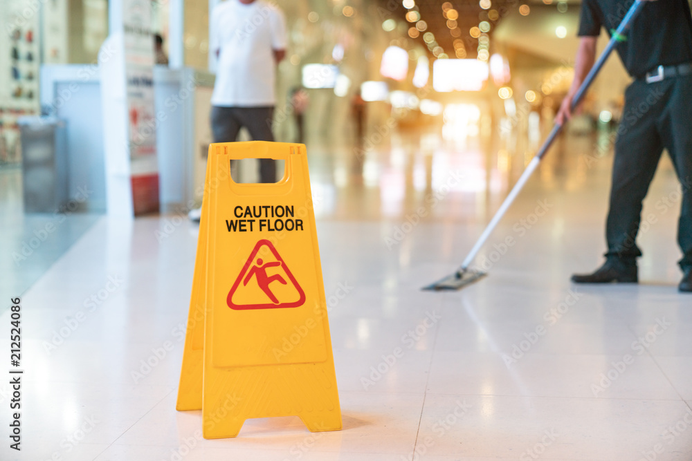 Fototapety, obrazy: Low Section Of Worker Mopping Floor With Wet Floor Caution Sign On Floor