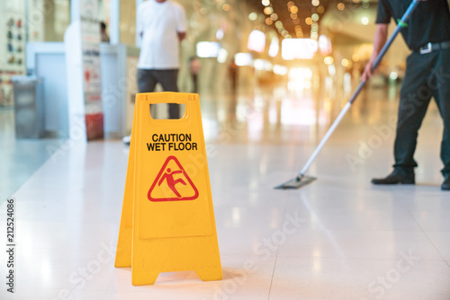 Fotografia  Low Section Of Worker Mopping Floor With Wet Floor Caution Sign On Floor