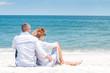 Honeymoon. Happy couple sitting on tropical beach.