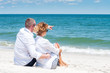 Happy couple sitting on tropical beach.