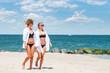 Two happy girls in bikini on the beach. Best friends walking on the beach