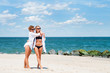 Two happy girls in bikini on the beach. Best friends having fun, summer vacation holiday lifestyle.