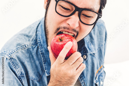 Handsome man eating and biting red apple. Healthy natural food concept