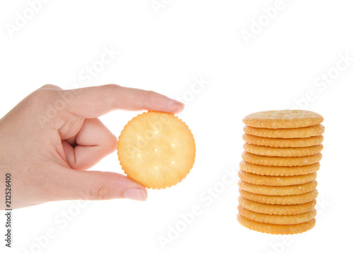 Fotografie, Obraz  Round salted crackers stacked with young caucasian hand holding a single cracker next to pile