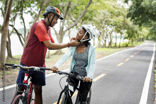 Man fastening the bike helmet for his girlfriend Canvas Print