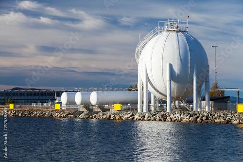 Cuadros en Lienzo Spherical gas holder stands on sea coast