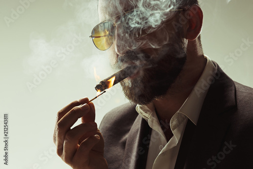 Fotografie, Tablou  The barded man in a suit holding cigar