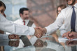 handshake of business partners on the background of the deskto