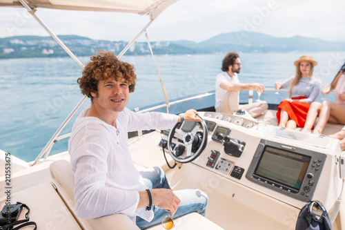 Foto Young handsome curly captain navigatong sailing boat and looking at camera, grou