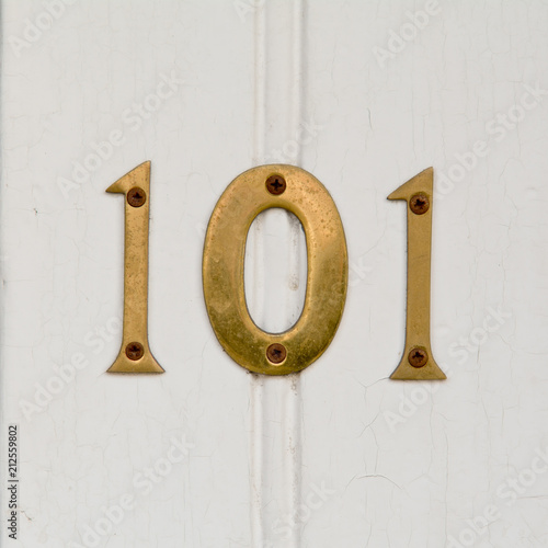 Brass house number 101 sign on door Poster