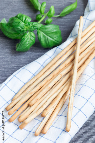Traditional Italian snack grissini bread sticks with basil leaves on background, vertical
