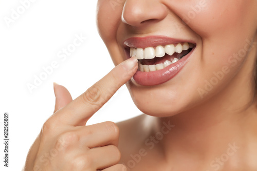 Fotografie, Obraz  young woman touchng her teeth with her finger on white background