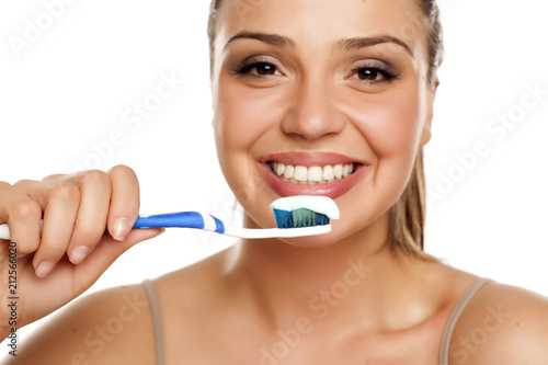 Spoed Foto op Canvas Wanddecoratie met eigen foto young smiling woman holding a toothbrush on white background