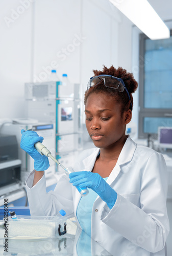 Carta da parati African-american scientist or graduate student in lab coat loading samples with