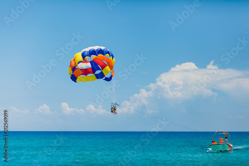 Poster Water Motor sports People flying on a colorful parachute towed by a motor boat