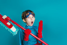 Portrait Of Young Boy Cleaning Super Hero Hold Mop On Blue Background