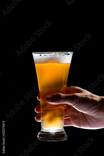 Foto op Plexiglas Bier / Cider Hand holding glass of craft beer on black background