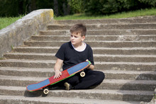 A Teenager With A Skateboard. Sits With A Skateboard Against The Backdrop Of A Stone Staircase.