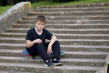 A Teenager With A Skateboard. Sits On A Skateboard Against The Backdrop Of A Stone Staircase.