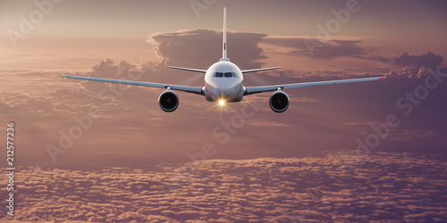 Commercial airplane flying above clouds. Wallpaper Mural